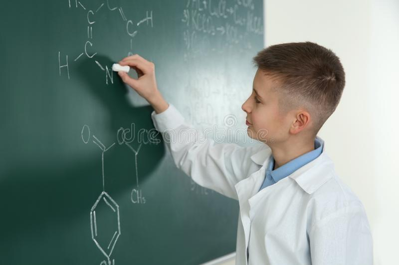 Schoolboy writing chemistry formula on blackboard royalty free stock image