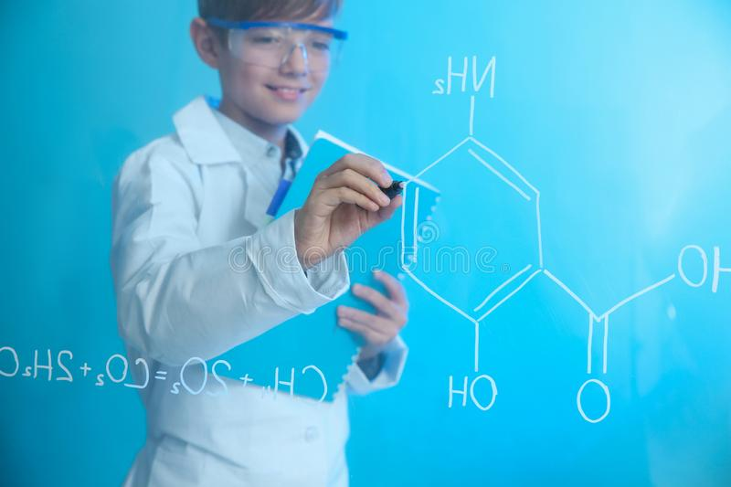 Schoolboy writing chemistry formula on glass board against color background royalty free stock images