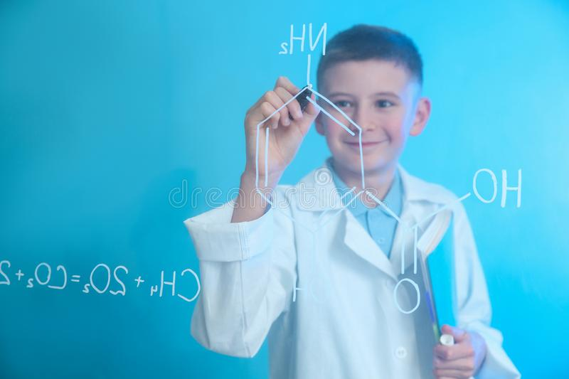 Schoolboy writing chemistry formula on glass board against color background royalty free stock photos