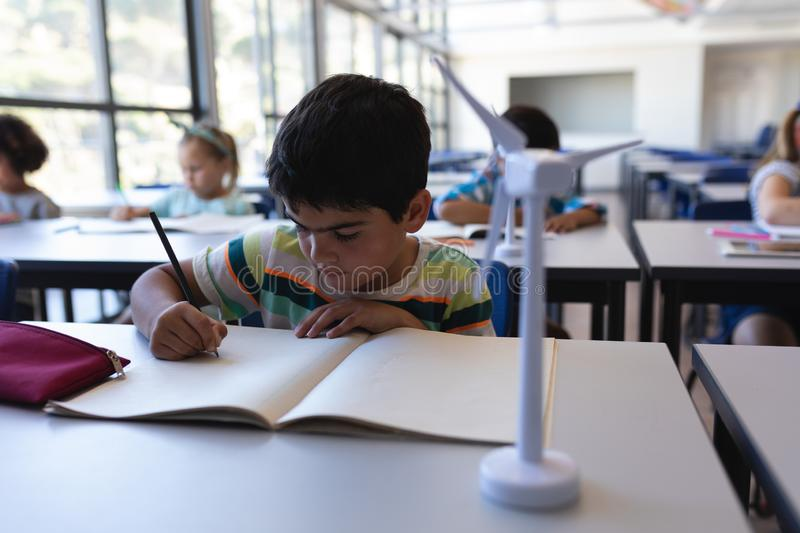 Schoolboy writing on notebook at desk in classroom stock photo