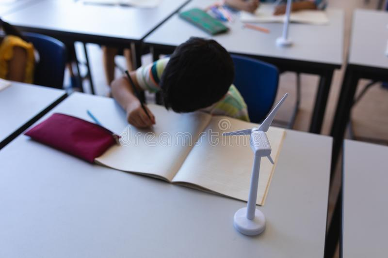 Schoolboy writing on notebook at desk in classroom stock image