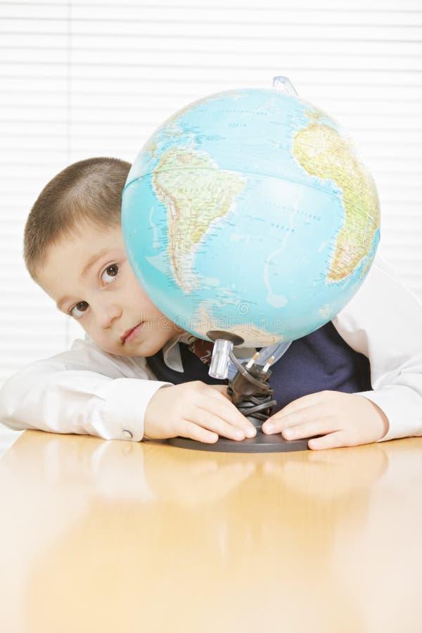 Schoolboynederlag bak jordklotet arkivbilder