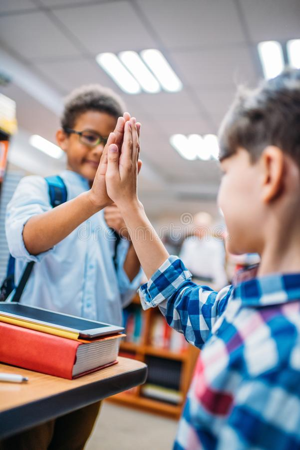 Close-up shot of schoolboys giving high five. At library royalty free stock image