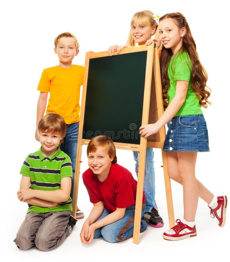 schoolboys och schoolgirls med blackboarden arkivbilder