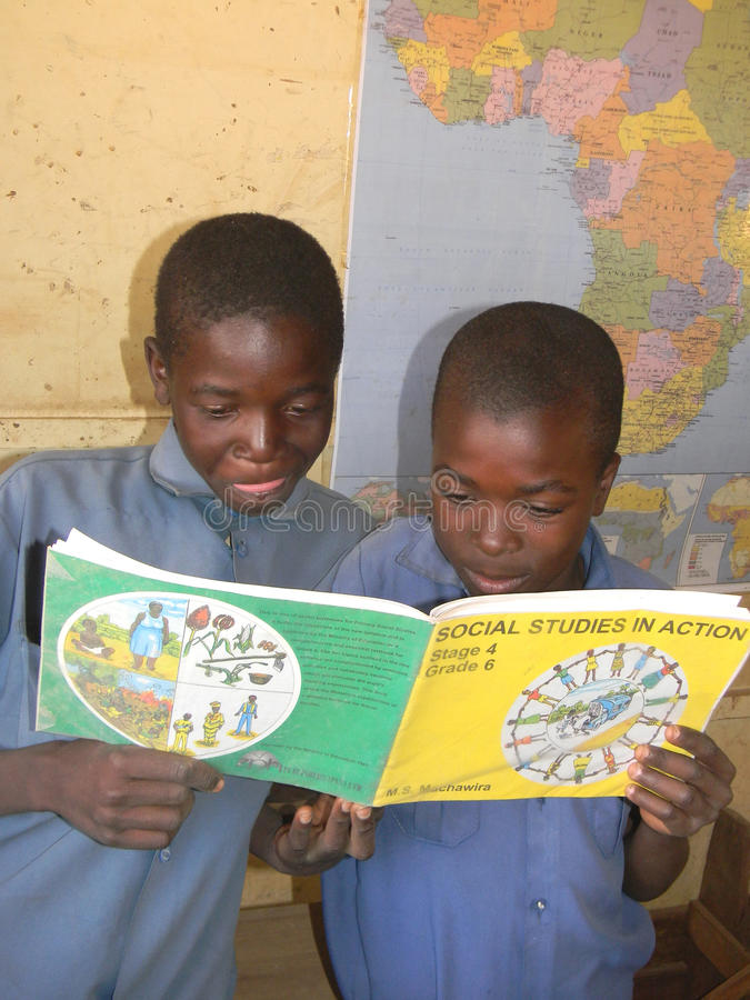 Schoolboys studying social studies book. Norton,Zimbabwe.July18 2015.Two primary schoolboys holding a Social Studies book while standing in front of the map of royalty free stock photo