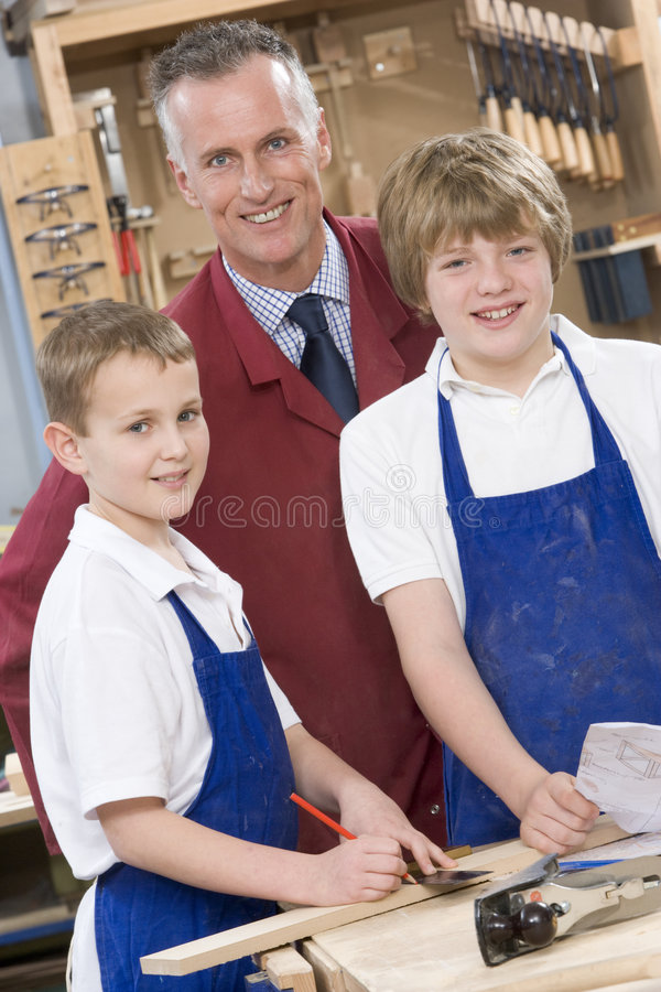Schoolboys and teacher in woodwork class. Smiling royalty free stock photo