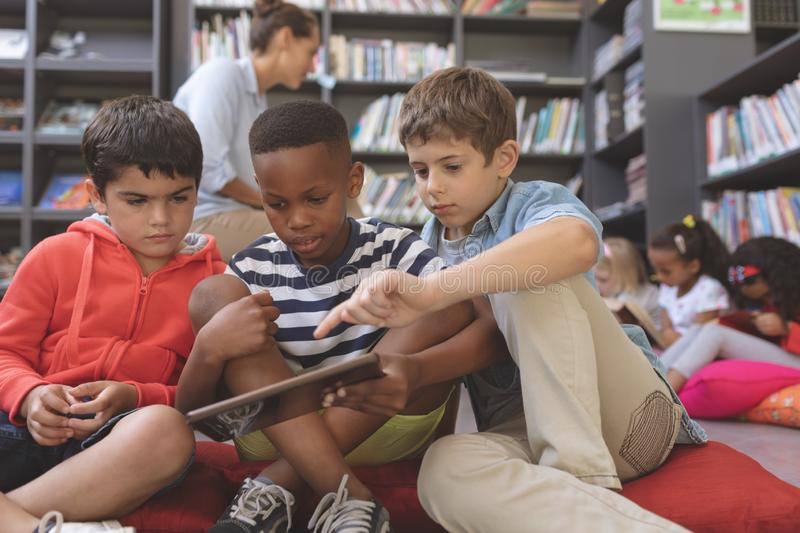 Schoolboys using a digital tablet while they are sitting on cushions in a library royalty free stock image