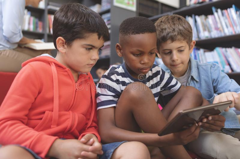 Schoolboys using a digital tablet while they are sitting on cushions in a library royalty free stock photo