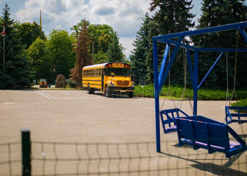Schoolbus door de school in de Oekraïne wordt geparkeerd die stock fotografie