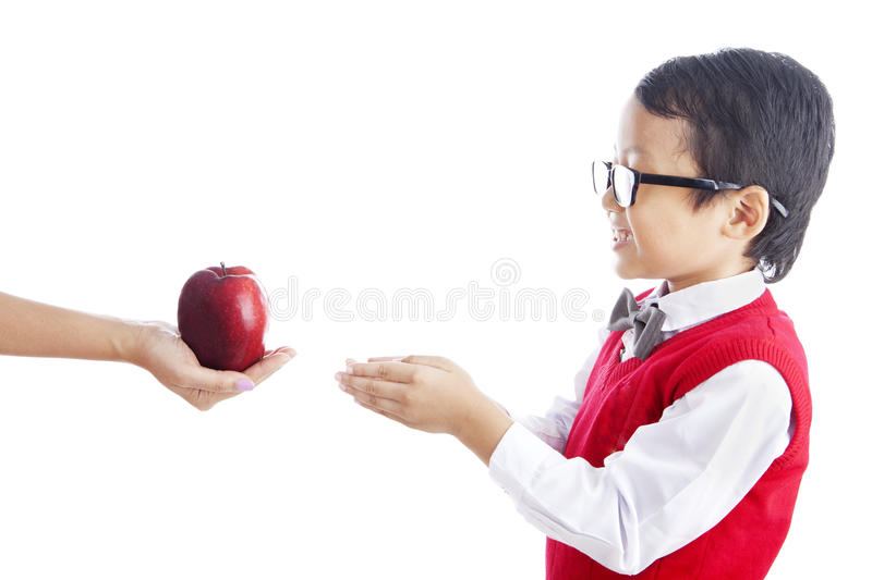 Schoolchild getting apple. Portrait of asian schoolchild receiving a red apple from his teacher. shot in studio isolated on white royalty free stock images