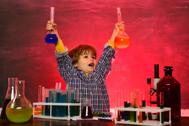 Schoolchild. School chemistry lessons. Happy little scientist making experiment with test tube. Happy smiling pupil stock images