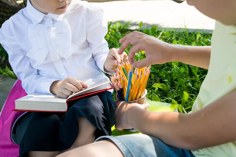 Schoolchildren a boy and a girl on the street take simple pencils from a glass. Schoolchildren a boy and a girl on  the street take simple pencils from a glass royalty free stock photos