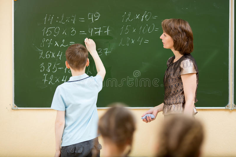 Schoolchildren in classroom at math lesson stock images