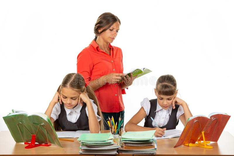 Schoolchildren at the desk do the assignment, the teacher in the background reads the assignment stock photography