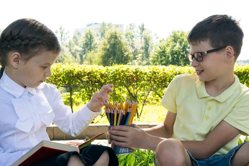 Schoolchildren doing their homework outdoors stock photos