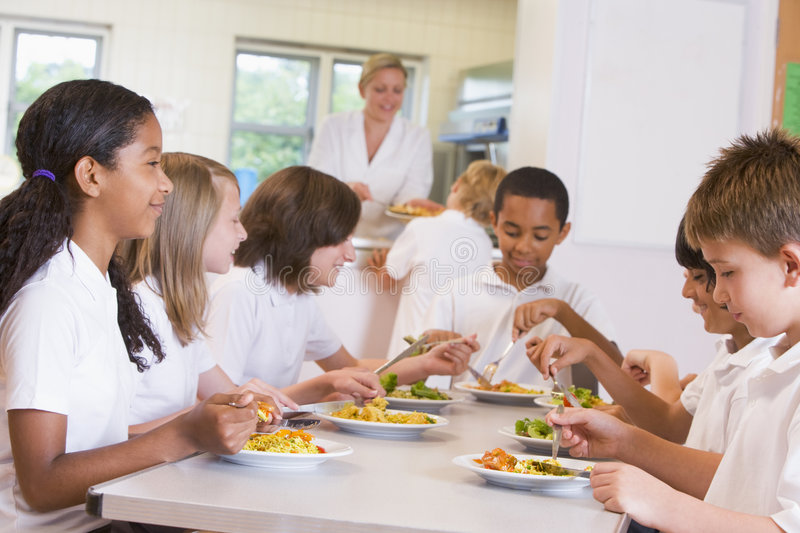 Schoolchildren enjoying their lunch in a school royalty free stock images