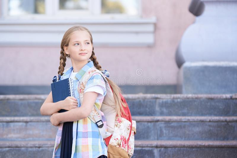 Schoolchildren girl back to school. Happy girl smile with little backpack stock photos