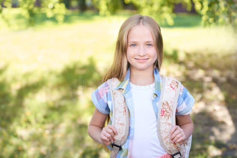 Schoolchildren girl back to school. Happy girl smile with little backpack stock images
