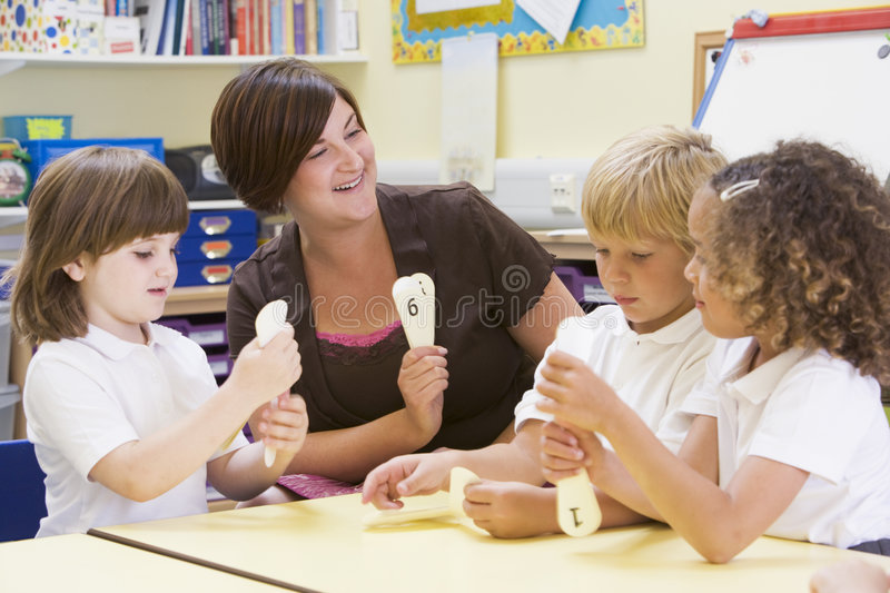 Schoolchildren learning numbers with their teacher royalty free stock photos