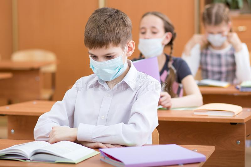 Schoolchildren with protection masks against flu virus at lesson in classroom royalty free stock images