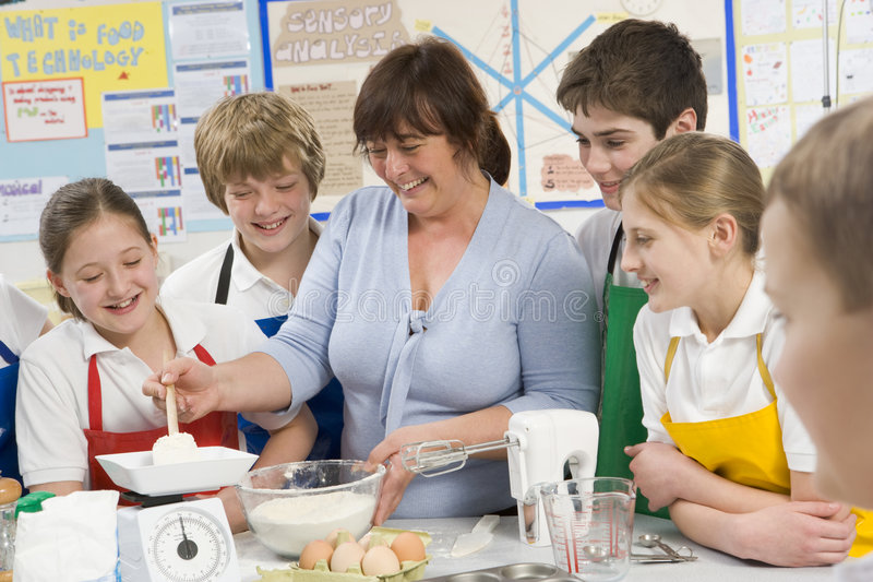 Schoolchildren and teacher in a cooking class royalty free stock photo
