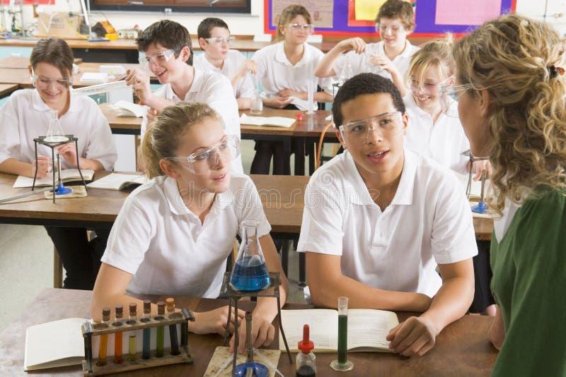 Schoolchildren and teacher in science class royalty free stock photo