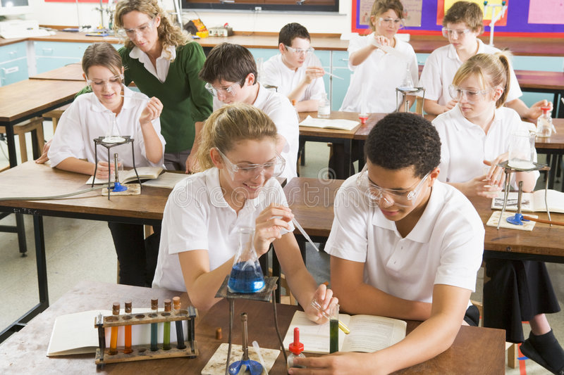 Schoolchildren and teacher in science class royalty free stock photography