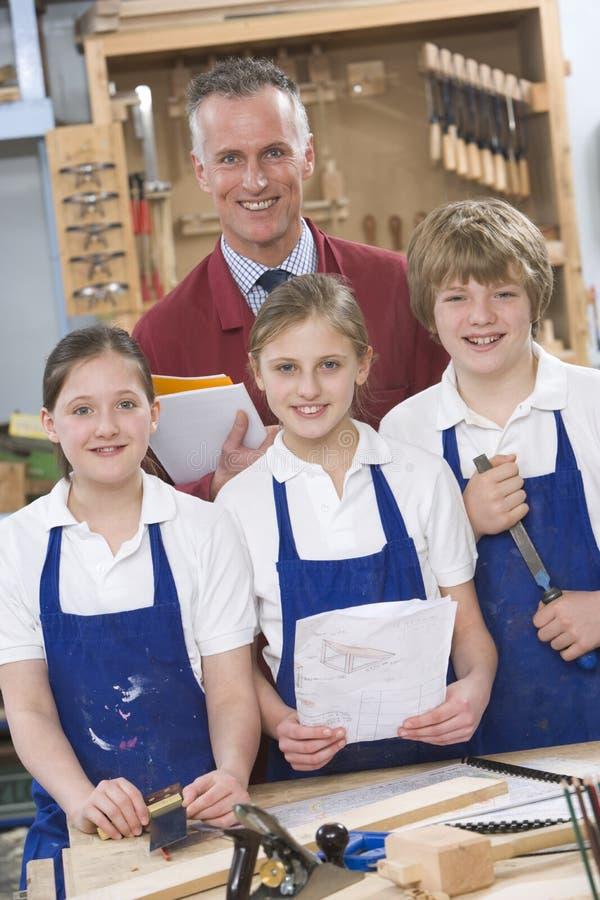 Schoolchildren and teacher in woodwork class royalty free stock photo
