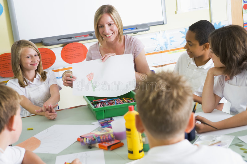 Schoolchildren and their teacher in an art class royalty free stock photos