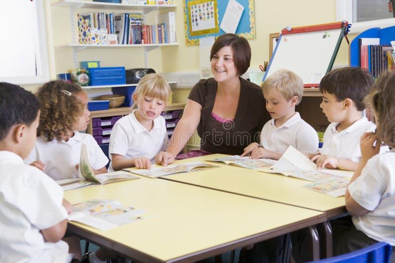 Schoolchildren and their teacher in class stock photography