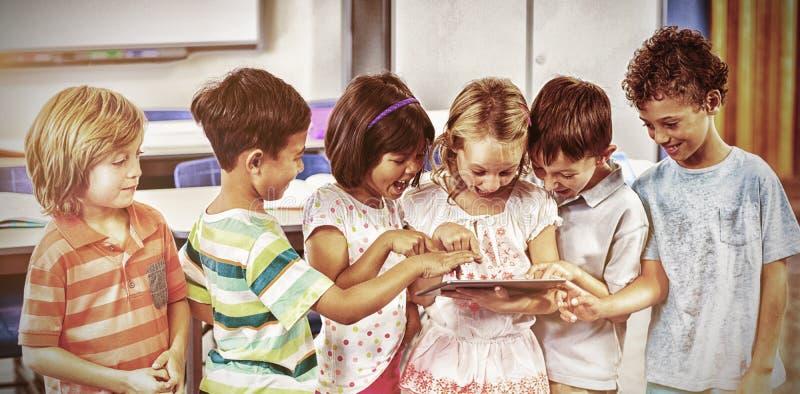 Schoolchildren using digital tablet royalty free stock photos