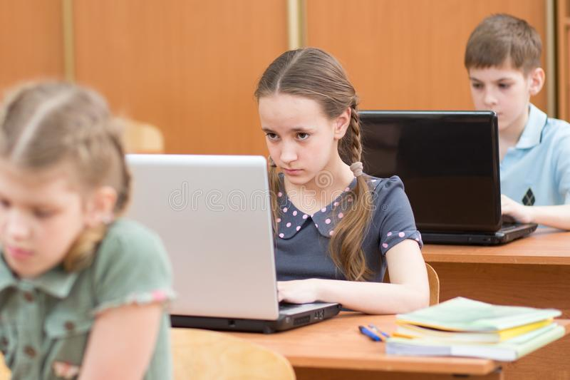 Schoolchildren using laptop at lesson in classroom royalty free stock images