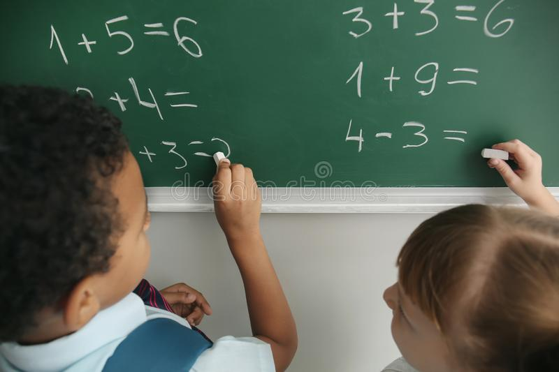 Schoolchildren writing on chalkboard in classroom during math lesson royalty free stock photos