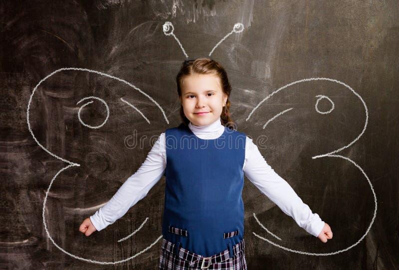 Schoolgirl against chalkboard, with butterfly wings. Cute little schoolgirl against chalkboard, with drawn butterfly wings stock image