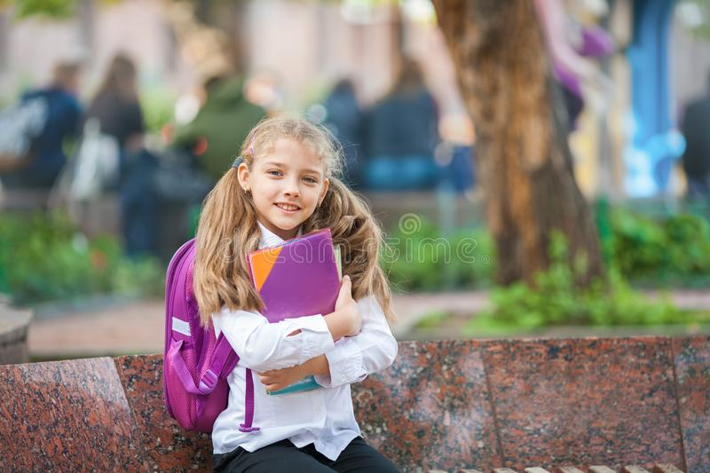 Schoolgirl with a backpack and book outdoors. Education and learning concept royalty free stock image