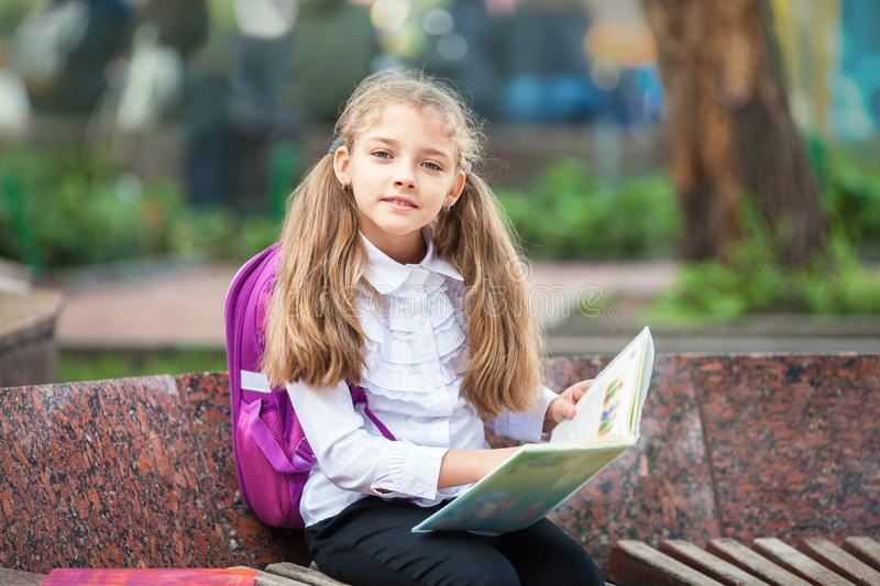 Schoolgirl with a backpack and book outdoors. Education and learning concept stock photography