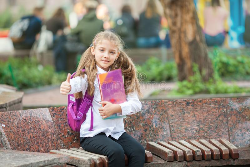 Schoolgirl with a backpack and book outdoors. Education and learning concept royalty free stock images