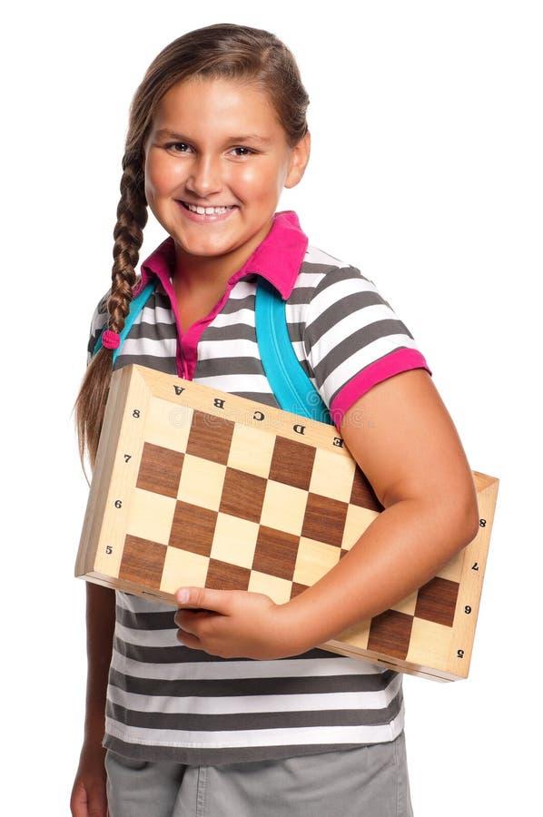 Schoolgirl with chessboard royalty free stock image