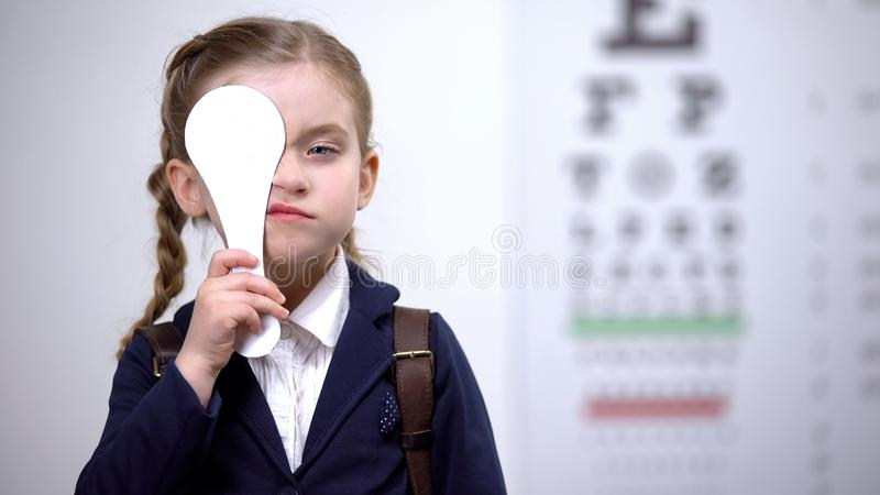 Schoolgirl closing one eye for complete vision exam, diagnostics of sight. Stock photo stock photo