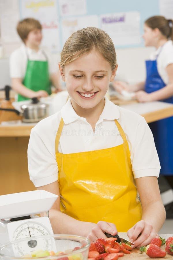 Schoolgirl in a cooking class stock images