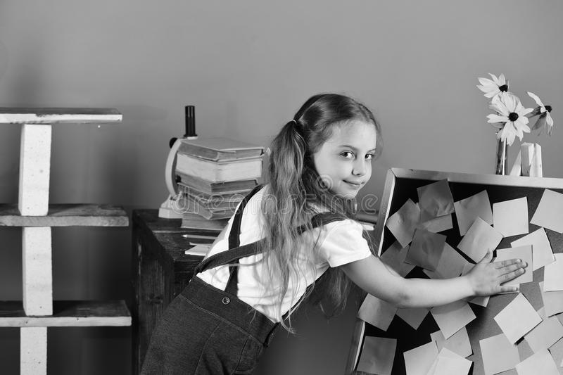 . Schoolgirl with cunning face in her classroom. Girl with ponytails puts sticky notes on blackboard near flowers stock photos