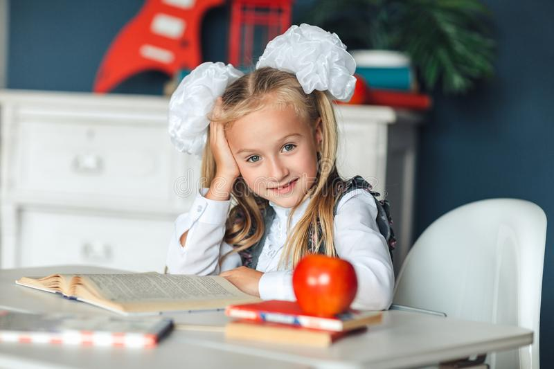Schoolgirl does not understand her homework. The little girl put her hand behind her head while reading a book. The difficulties. Of children`s education. The royalty free stock photo