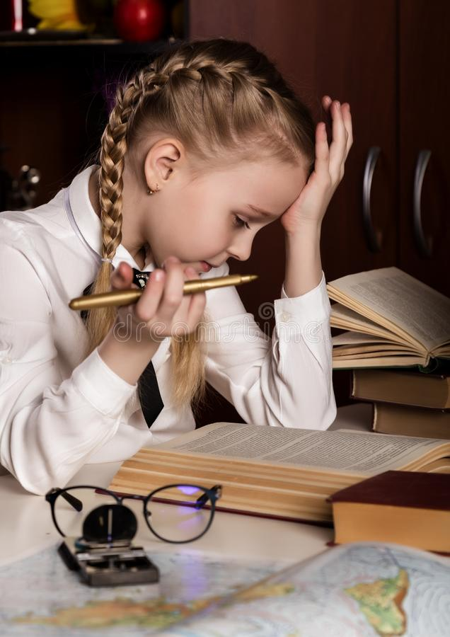 Schoolgirl doing homework, little blonde girl studing at home at the table. children`s education royalty free stock photo