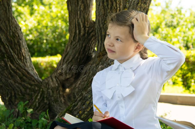 Schoolgirl doing homework in the park in the fresh air, thinking about the task and scratching her head, close-up royalty free stock images
