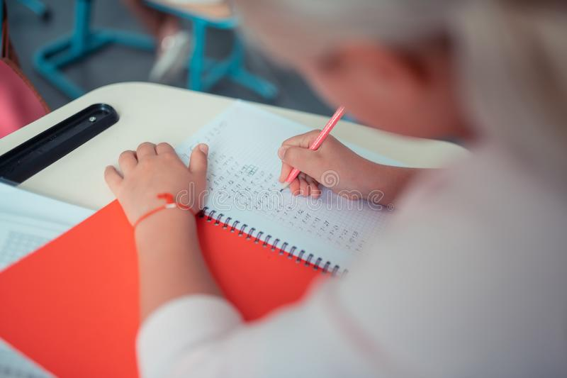 Schoolgirl doing sums in her red copybook. royalty free stock images