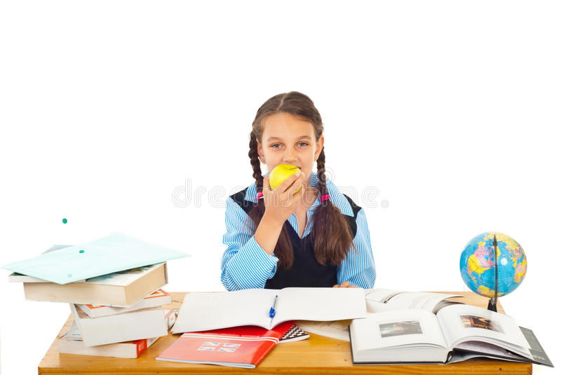 Schoolgirl eating apple. Schoolgirl sitting at pupil with books and notebooks and eating an apple isolated on white background royalty free stock images
