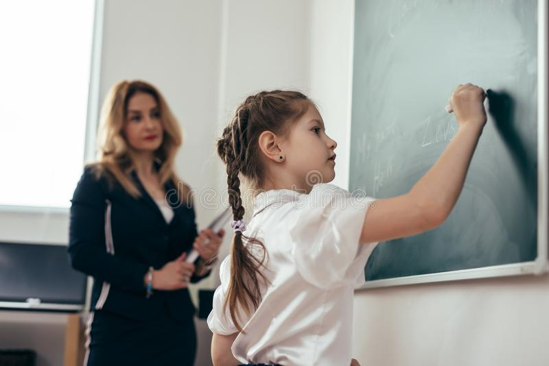 Schoolgirl first-grader writing on chalkboard. School lesson Teacher and pupil. stock photo