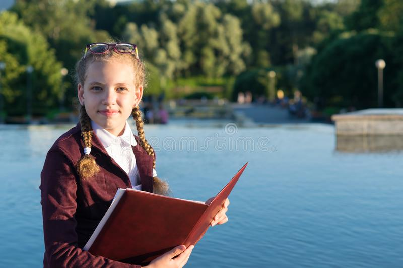 Schoolgirl with a folder sits by the water, place for an inscription royalty free stock images