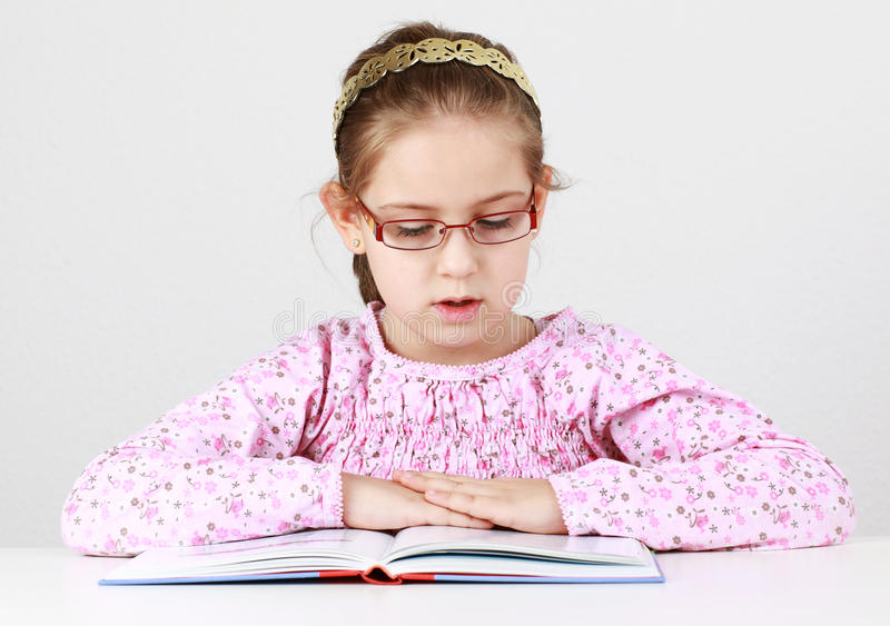 Schoolgirl with glasses reading book stock photography