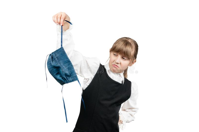 Schoolgirl has a disgust for the mask. Schoolgirl removes the mask in disgust, she is tired of quarantine, isolated on white background stock photo